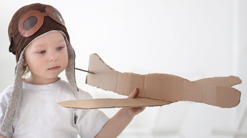 Boy with cardboard airplane